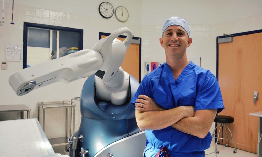 Dr. Scott Goldsmith posing in front of the robot used to assist in joint replacement procedures